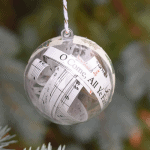 "A clear Christmas ornament with the song, ""O Come, All Ye Faithful"" inside."