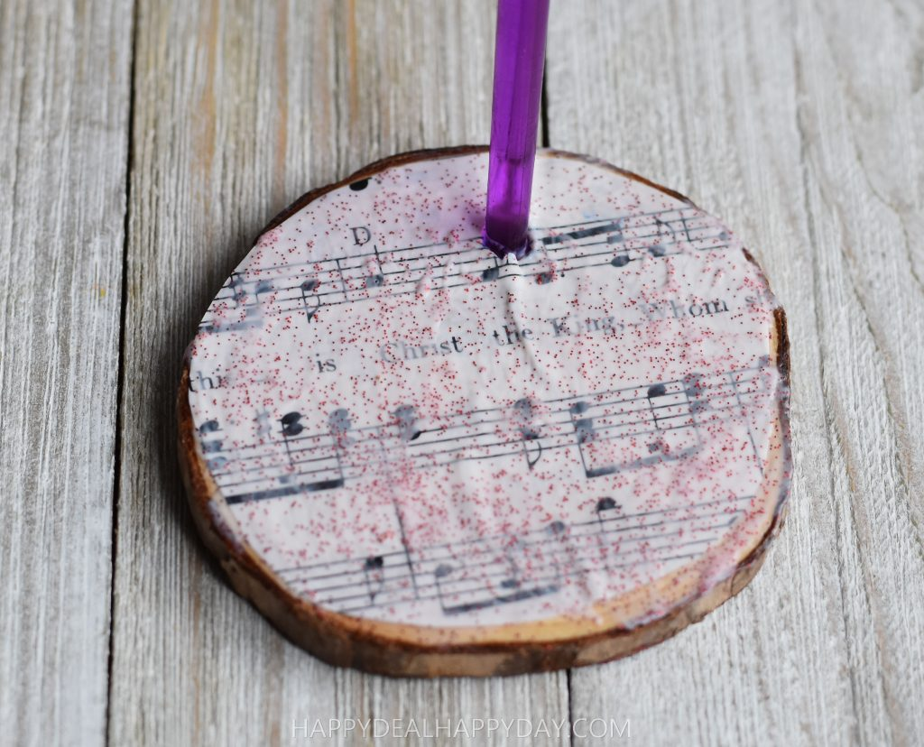 Punch a hole using paintbrush so you can hang your DIY Christmas ornament using thrift store books