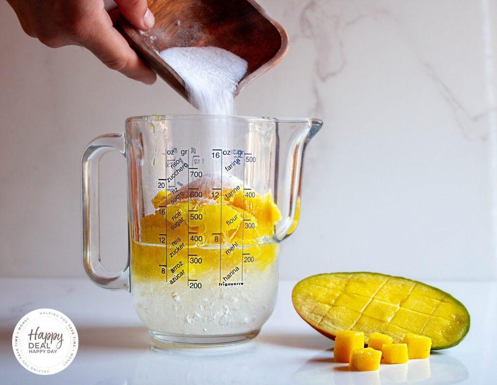 pouring sugar for mango slushie